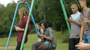 stock-footage-teens-on-cell-phones-teenagers-hanging-out-by-some-swings-and-using-mobile-phones